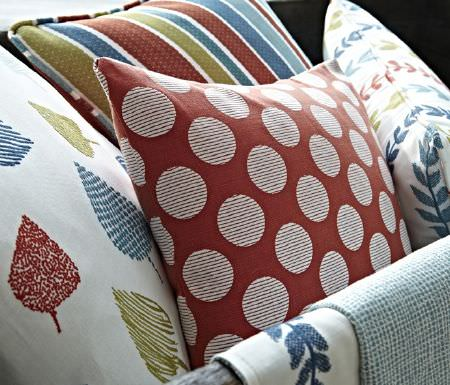 Prestigious Textiles -  Annika Fabric Collection - Coral red cushion with white dotted pattern, white cushions with colourful designs and striped cushion