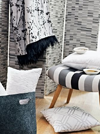 Prestigious Textiles -  Atrium Fabric Collection - A folding screen made in shades of grey, textured cushions, a grey, black and white striped stool and a patterned throw