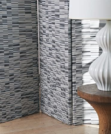 Prestigious Textiles -  Atrium Fabric Collection - A wooden occasional table with concave sides, a curved white table lamp, and a folding screen made in shades of grey