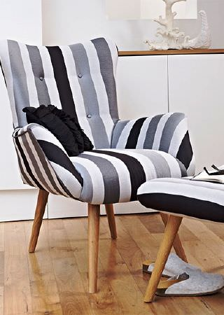 Prestigious Textiles -  Atrium Fabric Collection - Bold black, grey and white stripes covering a stylish armchair and footstool, both with wooden legs, and a black cushion