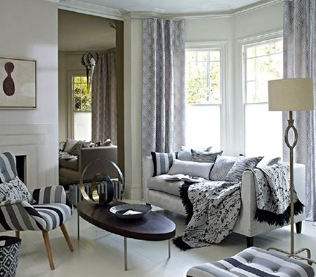 Prestigious Textiles -  Atrium Fabric Collection - White sofa, cream floor lamp, oval wood table, with an armchair, curtains and cushions in monochrome stripes and patterns