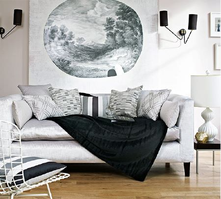 Prestigious Textiles -  Atrium Fabric Collection - A black throw with black, grey and white patterned cushions on a silver sofa, with a mesh chair, black table and a lamp