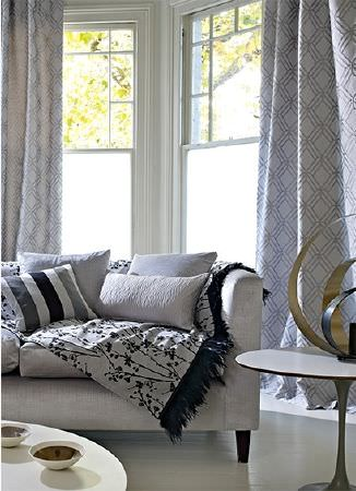 Prestigious Textiles -  Atrium Fabric Collection - A white sofa with a black and white printed throw, and subtly patterned curtains and cushions, beside two round white tables