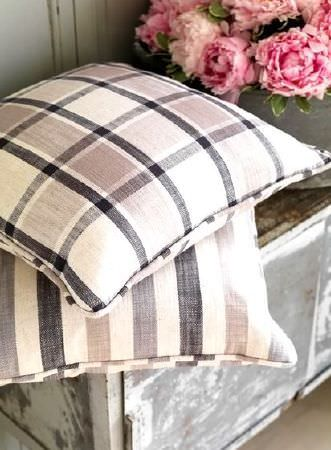 Prestigious Textiles -  Ayrshire Fabric Collection - Distressed chest beneath a cream, beige, grey and black striped cushion, a cushion with the same coloured checks and a green-grey flower pot