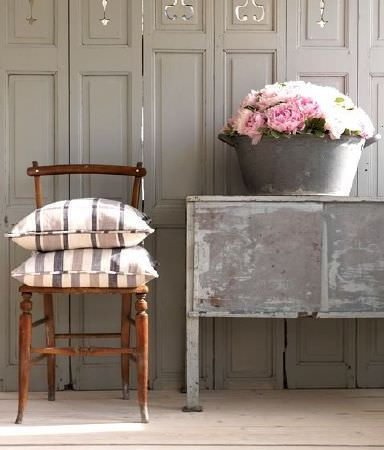 Prestigious Textiles -  Ayrshire Fabric Collection - Grey storage unit with a grey washtub style flower pot, with a brown wood chair and two striped and checked cushions