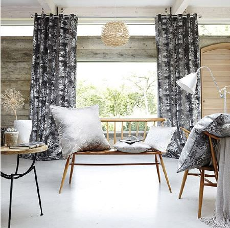 Prestigious Textiles -  Baroque Fabric Collection - Floor-length black and grey patterned curtains with grey and silver cushions on wooden chairs, with a lamp and small table