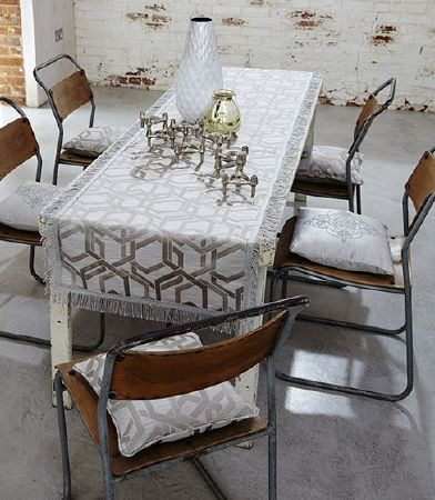 Prestigious Textiles -  Baroque Fabric Collection - Five dark wood and metal chairs, a rustic white table with a grey-beige patterned fringed runner and cushions, and vases