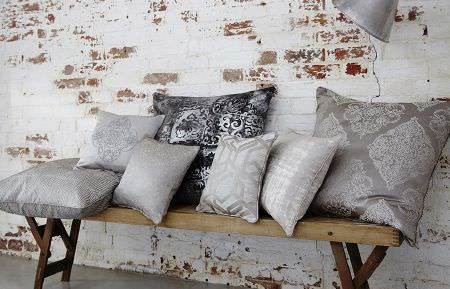 Prestigious Textiles -  Baroque Fabric Collection - Seven large and small scatter cushions patterned with dark grey, silver and white designs, on a wide rustic wooden bench