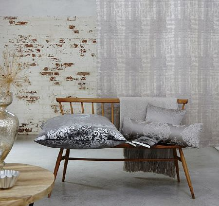Prestigious Textiles -  Baroque Fabric Collection - Wide, simple wooden seat with four grey and silver patterned cushions, with long grey-white curtains, a wood table and vases