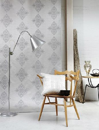 Prestigious Textiles -  Baroque Fabric Collection - Large silver floor lamp with a wooden chair, a white cushion, a silver and grey patterned backdrop, a round table and vases