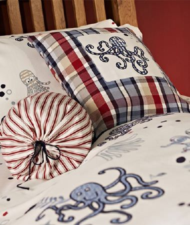 Prestigious Textiles -  Be Happy Fabric Collection - Fun blue octopuses as a large pattern on an off-white duvet and pillowcase, and as appliqué on a checked cushion, with a drawstring bag