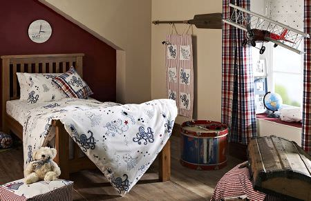 Prestigious Textiles -  Be Happy Fabric Collection - Octopus print bedding on a dark wood bed, with matching checked curtains,a footstool, cushion and wall hanging,with toys and wooden chest