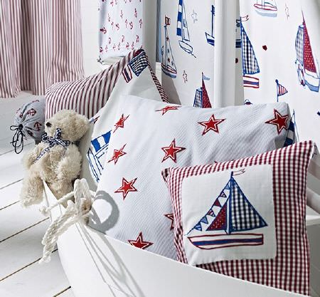 Prestigious Textiles -  Be Happy Fabric Collection - Red and blue sailboats on white fabric on a white boat