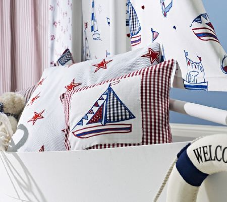 Prestigious Textiles -  Be Happy Fabric Collection - Scatter cushions featuring red, white and blue star prints, checks and sailboat shapes in the hull of a white boat with sailboat print sails