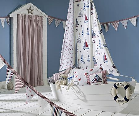Prestigious Textiles -  Be Happy Fabric Collection - A large white wood boat with sailboats printed on the sails, with patterned red, white and blue cushions, bunting, and long red and white curtains