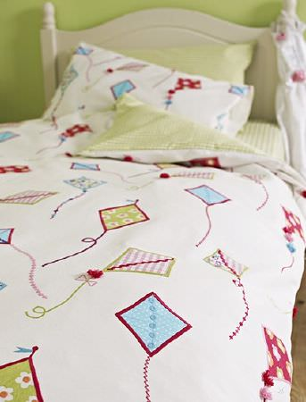 Prestigious Textiles -  Be Happy Fabric Collection - White duvet printed with blue, green, pink and red kites, with green checks on the reverse, matching sheet and pillowcases, on a cream bed