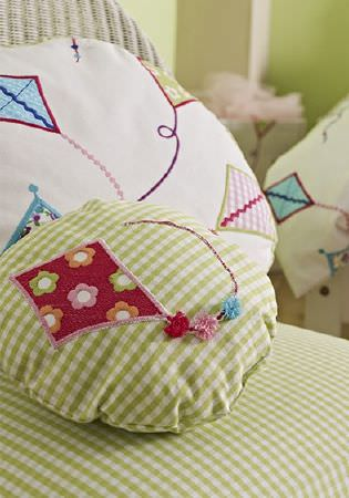 Prestigious Textiles -  Be Happy Fabric Collection - Round cushions, one in green checks with a floral red kits and 3D pompoms, one white with multicoloured kites, on a checked and wicker chair