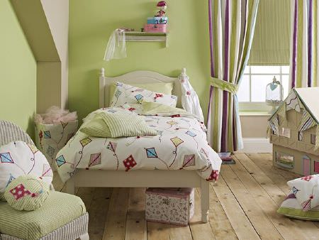 Prestigious Textiles -  Be Happy Fabric Collection - Green, white and purple striped curtains with green blinds, kite print bedding and cushions, green checked cushions and a cream wooden bed