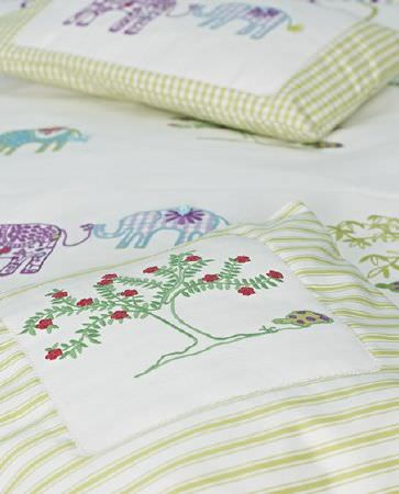 Prestigious Textiles -  Be Happy Fabric Collection - Designs of green trees and elephants in purple and blue on white fabric, appliquéd onto green and white checked cushions