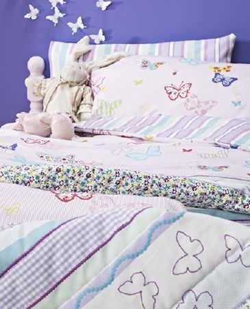 Prestigious Textiles -  Be Happy Fabric Collection - Butterfly print fabric and bedding in several styles, with co-ordinatingblue, purple and white striped and floral print fabrics, on a white bed
