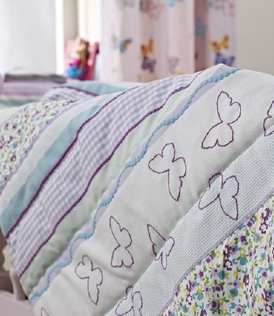 Prestigious Textiles -  Be Happy Fabric Collection - A quilt made up from fabrics in white, blue, purple and green colours, with butterfly prints, wavy lines, florals, checks and plain colours