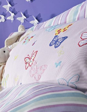 Prestigious Textiles -  Be Happy Fabric Collection - Light purple pillowcase with large, multicoloured butterflies, withmore bedding and pillowcases striped in shades of white, purple and blue