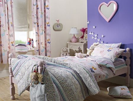 Prestigious Textiles -  Be Happy Fabric Collection - Striped quilt made up of several fabrics onbutterfly print bedding, striped sheets, a white wood bed, with table and butterfly print curtains