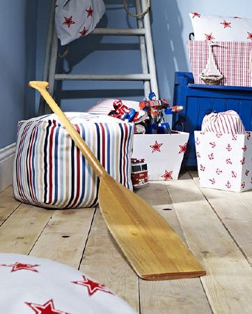 Prestigious Textiles -  Be Happy Fabric Collection - Wooden oar with a star print box and cushions, a white box with small red anchors, a multicoloured striped cubed footstool and a wooden ladder