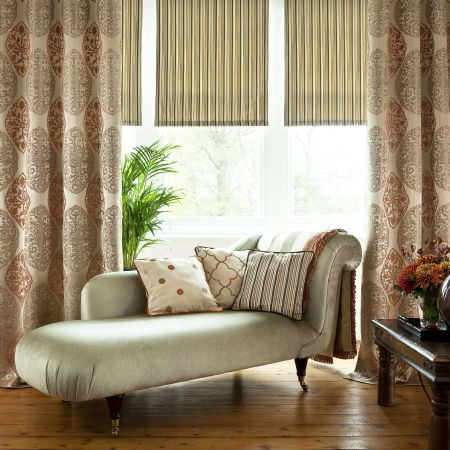 Prestigious Textiles -  Berber Fabric Collection - A chaise longue in a luxurious room with ornate cushions and curtains in colours of cream and yellow and red