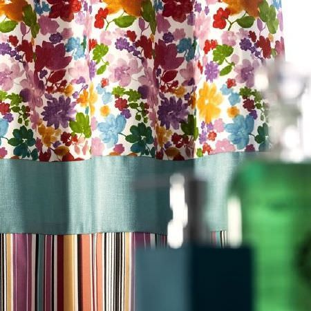 Prestigious Textiles -  Blossom Fabric Collection - Brightly coloured floral and striped fabrics, separated and connected by a strip of turquoise satin effect fabric, with hand wash dispensers