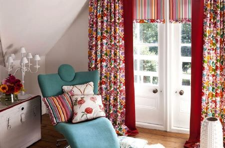 Prestigious Textiles -  Blossom Fabric Collection - Curtains with a busy multicoloured flower print and red trim, striped blinds, blue reclining chair, coloured cushions, white vase and lamp
