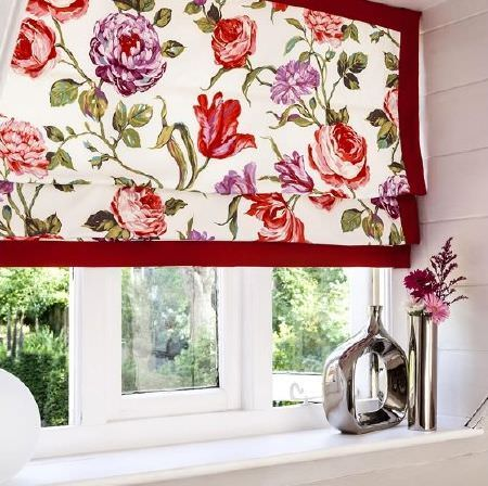 Prestigious Textiles -  Blossom Fabric Collection - Cream blinds with a large red and magenta flower pattern and a deep red trim, with a silver cylindrical vase and a silver