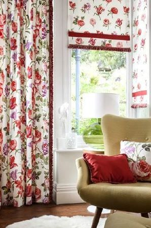 Prestigious Textiles -  Blossom Fabric Collection - Cream, red, pink and green curtains and blinds with red fringing, a matching cushion, a plain red cushion ad an olive green armchair
