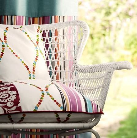 Prestigious Textiles -  Blossom Fabric Collection - White woven wicker style chair, with multicoloured cushions featuring dots, stripes and florals, and stripy curtains