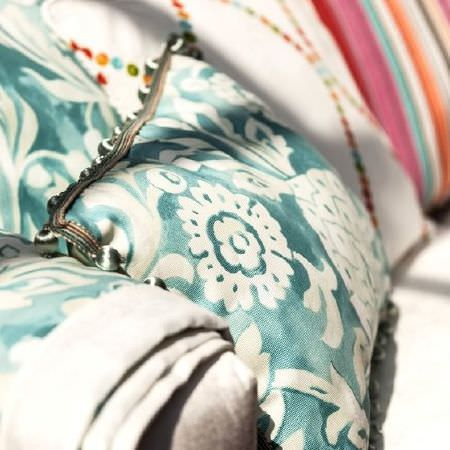 Prestigious Textiles -  Blossom Fabric Collection - Rectangular cushion in turquoise and white, with matching fabric, a white cushion with multicoloured dots, and a coloured striped cushion