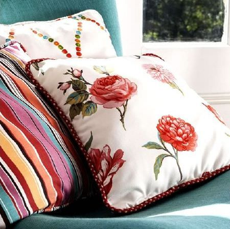 Prestigious Textiles -  Blossom Fabric Collection - Cushions featuring brightly coloured stripes, dots on a cream background, red and pink roses on a cream background, all on a turquoise chair