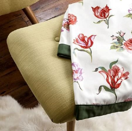 Prestigious Textiles -  Blossom Fabric Collection - Green edged traditional floral print fabric, on a chair made with hard-wearing light green fabric, with a soft, fluffy white rug