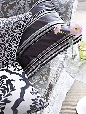 Prestigious Textiles -  Boutique Fabric Collection - Round table with vases beside a grey and white patterned sofa, and four black, grey and white patterned and striped cushions