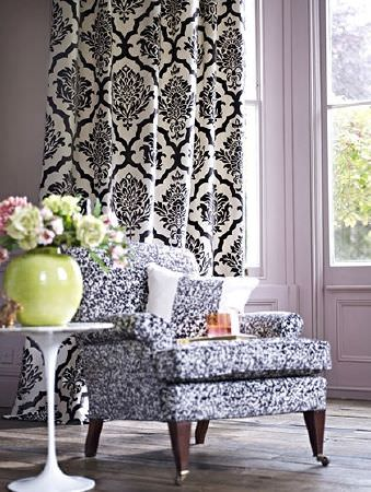 Prestigious Textiles -  Boutique Fabric Collection - Long curtains with an ornate black and cream pattern, a dark grey and white armchair, a white table and large green vase