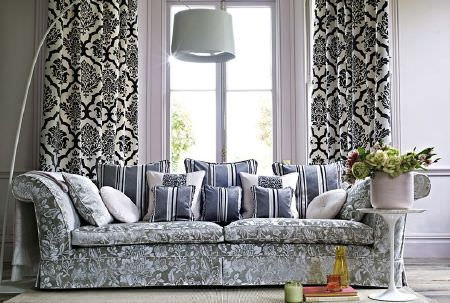 Prestigious Textiles -  Boutique Fabric Collection - Different shades of grey and white making up a patterned sofa and curtains, striped cushions, and a large lamp and round table