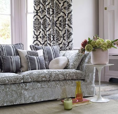 Prestigious Textiles -  Boutique Fabric Collection - A small table and vases beside a grey and white patterned sofa with striped scatter cushions, and black and cream curtains