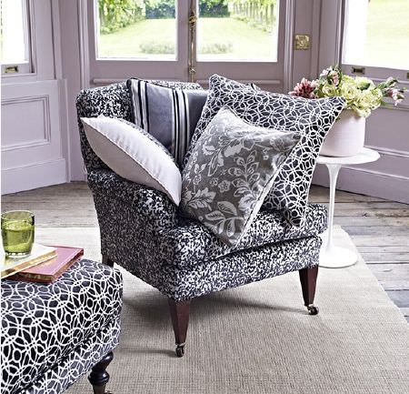 Prestigious Textiles -  Boutique Fabric Collection - Black and white patterned armchair, footstool and cushions, with grey and white cushions, and a small round white table