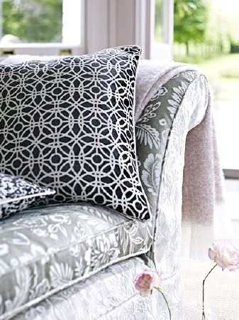 Prestigious Textiles -  Boutique Fabric Collection - Grey and white floral patterned sofa with two black and white patterned scatter cushions and a pink-grey and cream throw