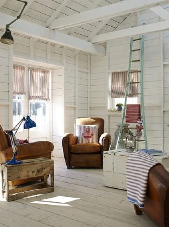 Prestigious Textiles -  Brighton Fabric Collection - Distressed leather armchairs with nautical cushion, striped blinds and fabric, wood table and trunk, blue and black lamps, and a ladder