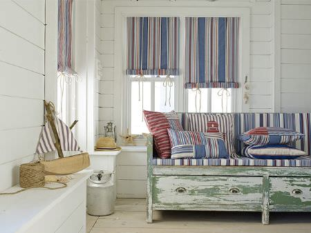 Prestigious Textiles -  Brighton Fabric Collection - Distressed green wood bench with drawers underneath blue and white striped seat and scatter cushions, striped blinds, metal can, toy boat