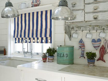 Prestigious Textiles -  Brighton Fabric Collection - Blue and white striped blind with eyelets, domed silver light shades, padded fish and heart in striped fabrics, tin mugs, metal bread bin
