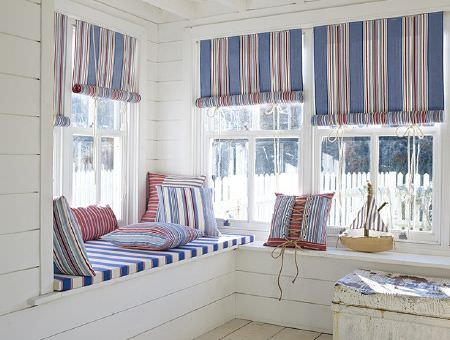 Prestigious Textiles -  Brighton Fabric Collection - Striped roll-up blinds, with a blue and white striped bench seat cushion, cushions in blue, red and white stripes, white trunk, and toy boat