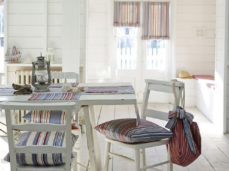 Prestigious Textiles -  Brighton Fabric Collection - White wood table and chairs with blue, white and red striped cushions, table runner, place mats, blinds, drawstring bag, and silver lantern