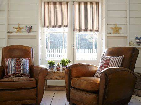 Prestigious Textiles -  Brighton Fabric Collection - Rustic leather armchairs in two different styles, striped roll-up blinds, striped appliqued and lace-up cushions, and a rustic wood table
