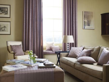 Prestigious Textiles -  Britannia Fabric Collection - Sandy coloured upholstered couch with purple pillows with classical designs, purple curtains, and a striped bench seating pad and tablecloth